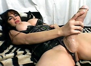 Busty mistress lies in the bed, stroking gigantic strap-on.