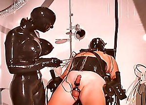 Two latex dominas training their mature slave practicing cbt session on him