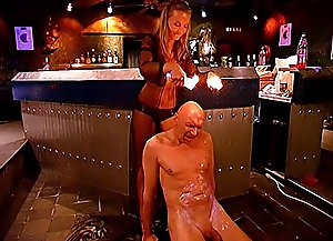 Beautiful fetish mistress who owns a famous femdom bar pours hot wax on her slave's bald head, big cock and balls