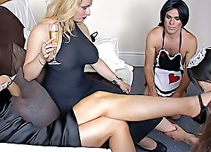 Two femdom queens enjoy their own cross-dressing party having two men in sexy maid outfits lick their toes and soles